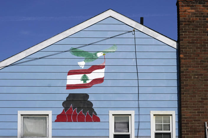 A bald eagle flying with the Lebanon flag over the Beirut port blast is depicted on Samih Zreik's house, Thursday, Nov. 19, 2020, in Dearborn, Mich. Zreik painted his house in tribute to Lebanon following the blast at Beirut's port that killed nearly 200 people, wounded more than 6,000 and caused billions of dollars in damage. (AP Photo/Carlos Osorio)