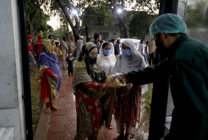 A worker from Saylani Welfare Trust gives free food to women for breaking their fast on the first day of Ramadan, in Islamabad, Pakistan, April 25, 2020. (AP Photo/Anjum Naveed)