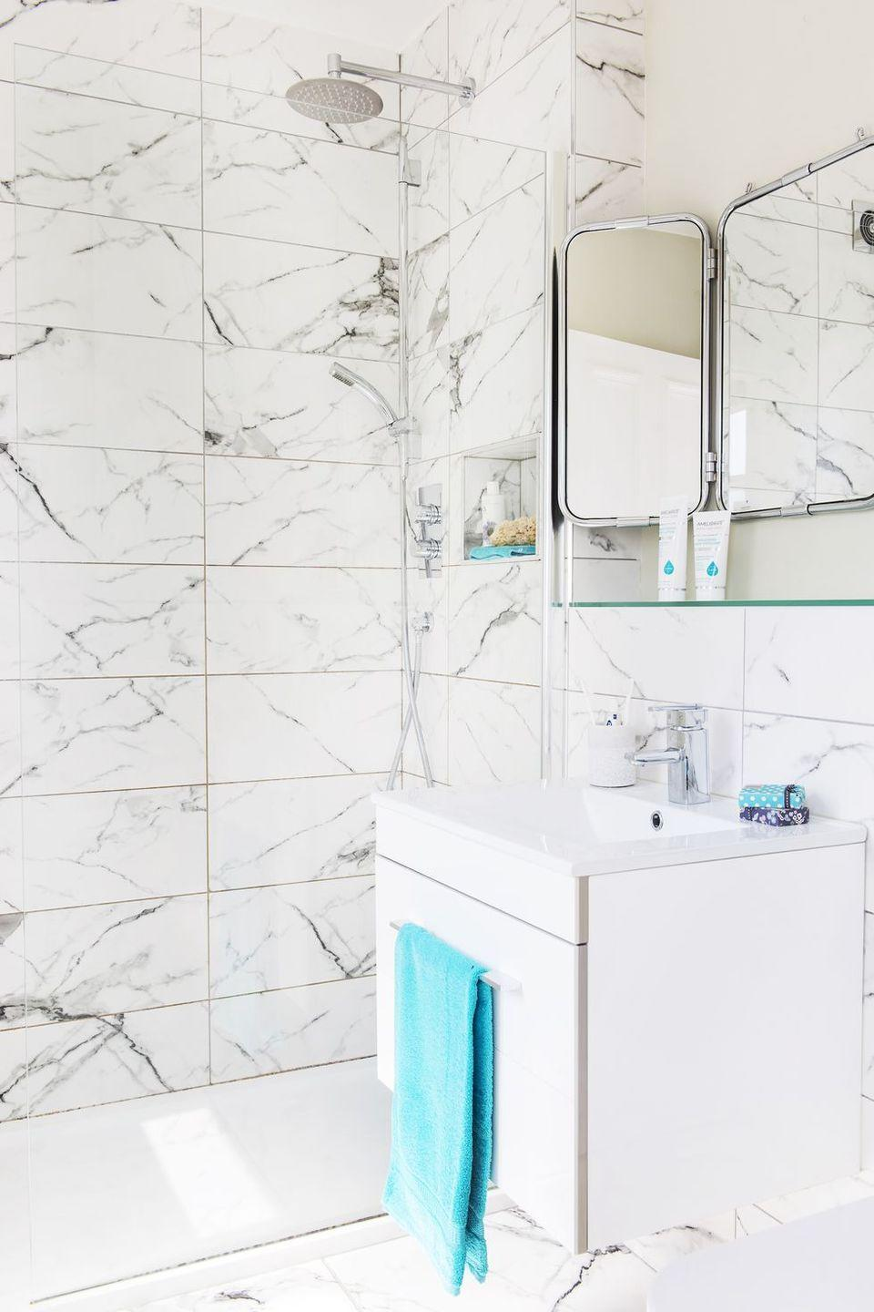 <p>White marble with light gray veins adds a sophisticated elegance to this shower design. </p>