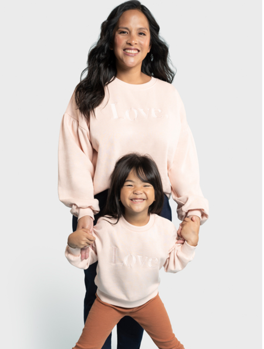 a mother and daughter wearing matching pink love sweater jumpers for mothers day