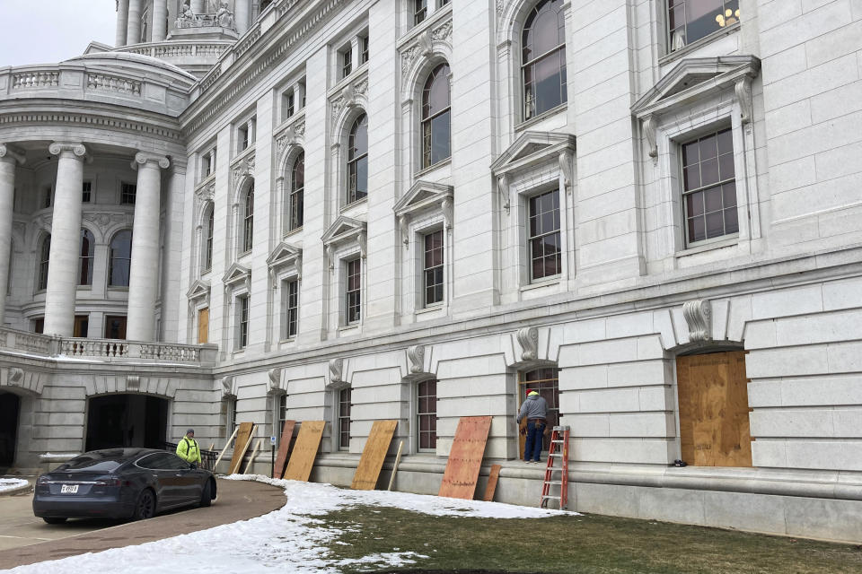 Workers begin boarding up the Wisconsin state Capitol building in Madison on Monday, Jan. 11, 2021. State officials are concerned about the prospects of state-centered violence in the wake of last week's security breaches at the U.S. Capitol. (AP Photo/Todd Richmond)
