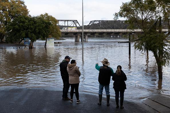 People look on as heavy flooding is seen along the Shoalhaven River in Nowra.