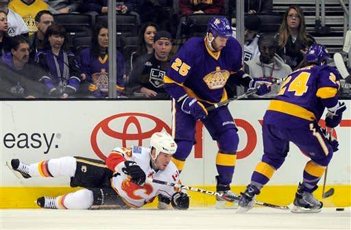 Calgary Flames defenseman Scott Hannan, left, falls to the ice as Los Angeles Kings center Colin Fraser, right, controls the puck as left wing Dustin Penner trails the play during the first period of their NHL hockey game, Saturday, Feb. 18, 2012, in Los Angeles. (AP Photo/Mark J. Terrill)