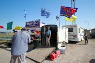 Motorcycle riders on their way to the Sturgis Motorcycle Rally stop at a stand selling Trump displays in Wall, S.D., on Saturday, Aug. 8, 2020. The group has taken advantage of recent motorcycle rallies, which have been some of the largest mass gatherings in the country, to make direct appeals to register to vote. While the group has gained a significant online following for its shows of bravado, it remains to be seen if they can get ballot boxes filled with bikers, many who hail from the suburbs. (AP Photo/Stephen Groves)