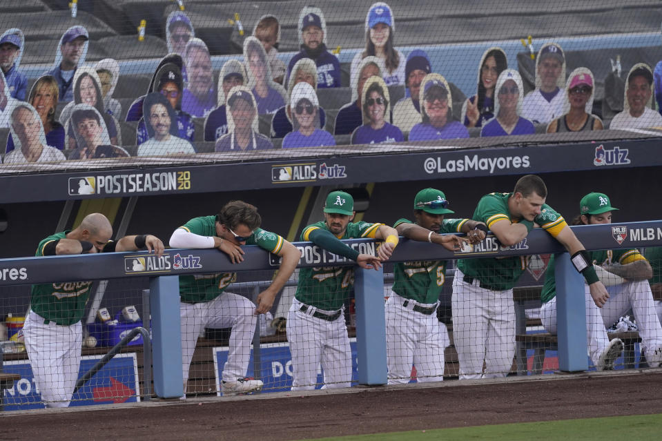 Oakland Athletics players stand in the dugout during the ninth inning of Game 2 of a baseball American League Division Series against the Houston Astros in Los Angeles, Tuesday, Oct. 6, 2020. (AP Photo/Ashley Landis)