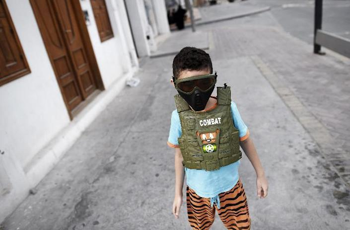 A young Bahraini boy wears a toy mask and protection vest in the street during clashes with police following a demonstration to mark the fourth anniversary of the Arab Spring-inspired uprising on February 14, 2015, in Daih on the outskirts of Manama (AFP Photo/Mohammed al-Shaikh)