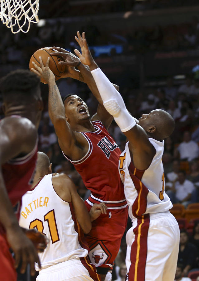 Miami Heat's Dwyane Wade (3) blocks a shot by Chicago Bulls' Derrick Rose during the second half of an NBA basketball game in Miami, Tuesday, Oct. 29, 2013. The Heat won 107-95. (AP Photo/J Pat Carter)