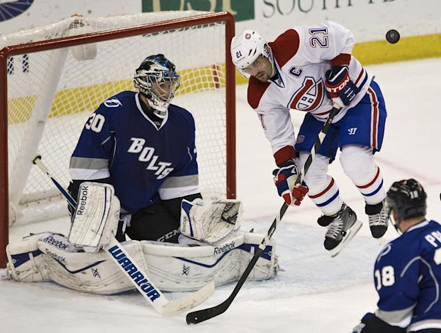 Montreal Canadiens' Brian Gionta (21) leaps away from a shot on goal as he blocks Tampa Bay Lightning's Ben Bishop (30) during the second period of an NHL hockey game Saturday, Dec. 28, 2013, in Tampa, Fla. (AP Photo/Steve Nesius)