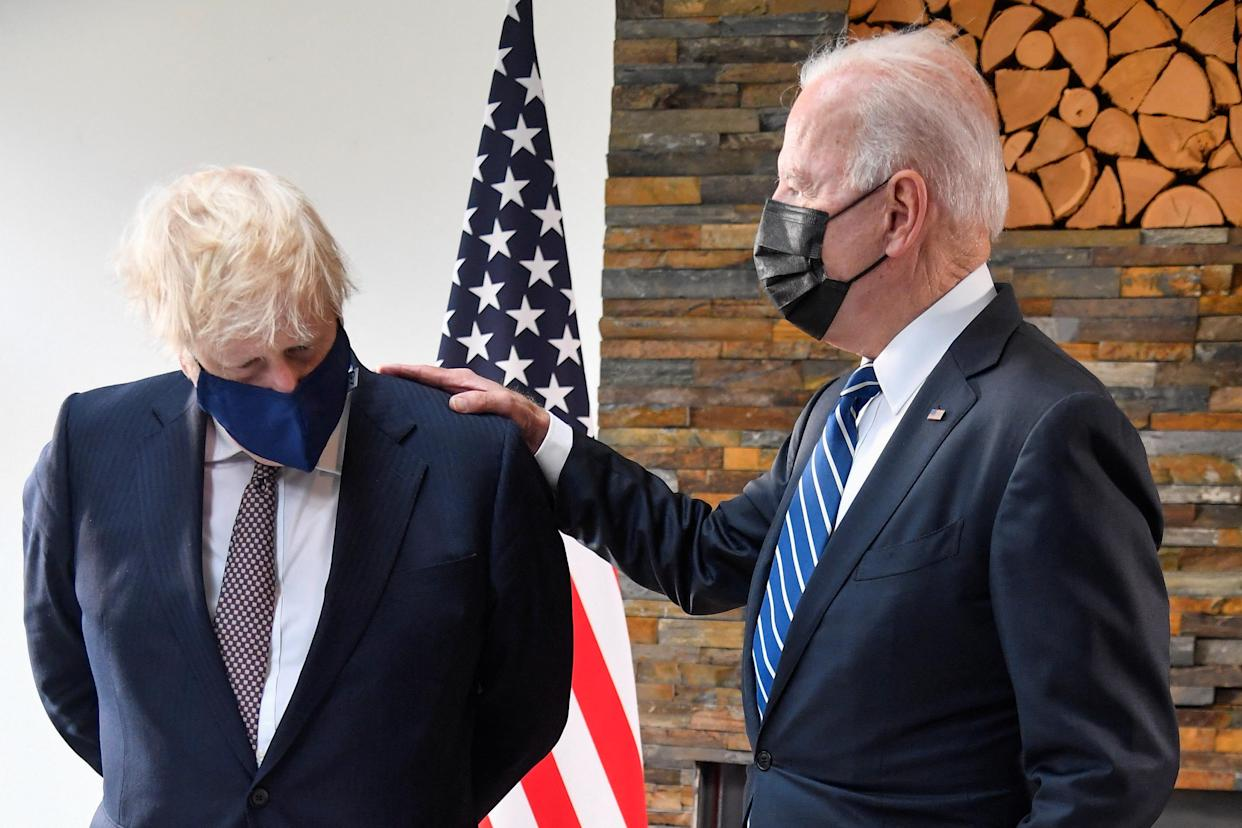 TOPSHOT - Britain's Prime Minister Boris Johnson (L) and US President Joe Biden, wearing face coverings due to Covid-19, view documents relating to the Atlantic Charter prior to a bi-lateral meeting at Carbis Bay, Cornwall on June 10, 2021, ahead of the three-day G7 summit being held from 11-13 June. - G7 leaders from Canada, France, Germany, Italy, Japan, the UK and the United States meet this weekend for the first time in nearly two years, for the three-day talks in Carbis Bay, Cornwall. (Photo by TOBY MELVILLE / POOL / AFP) (Photo by TOBY MELVILLE/POOL/AFP via Getty Images)