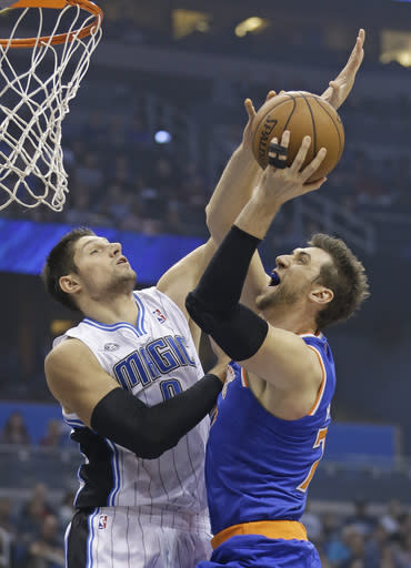 Orlando Magic's Nikola Vucevic, left, of Montenegro, tries to block a shot by New York Knicks' Andrea Bargnani, right, of Italy, in the first half of an NBA basketball game in Orlando, Fla., Monday, Dec. 23, 2013. (AP Photo/John Raoux)