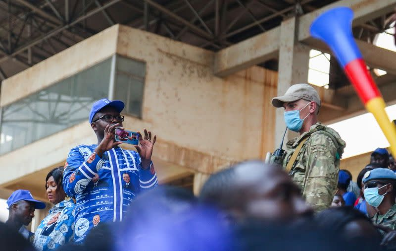 A Russian mercenary stands guard as Central African Republic President Faustin Archange Touadera addresses supporters at a political rally at the stadium in Bangui