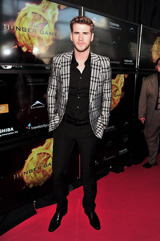 """A day earlier, Miley's main squeeze, Liam Hemsworth -- who plays Gale Hawthorne in """"The Hunger Games"""" -- hit the red carpet for the film's Canadian premiere in Toronto. The strapping big-screen stud sported Gucci from head to toe, but his striped evening jacket was undoubtedly the standout element in his ensemble. (3/19/2012)"""