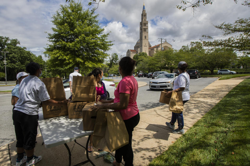 Area residents without a car wait in line for a ride after picking up food items distributed to families affected by the coronavirus pandemic at the Basilica of the National Shrine of the Immaculate Conception Friday, July 10, 2020, in Washington. The food distribution was hosted by the Catholic Charities of the Archdiocese of Washington. (AP Photo/Manuel Balce Ceneta)