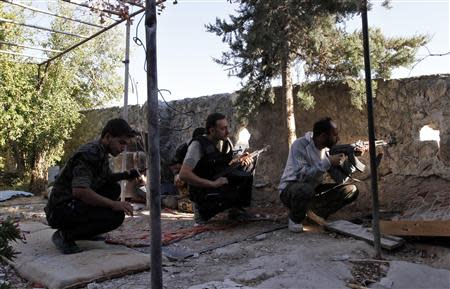 Free Syrian Army fighters take up positions with their weapons behind a wall in Aleppo's Sheikh Saeed neighbourhood