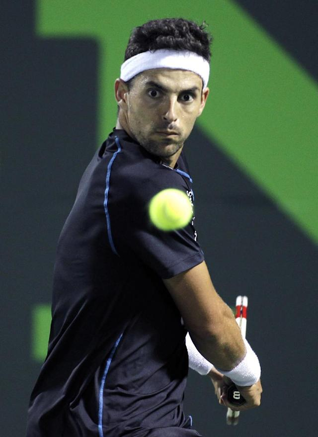 Santiago Giraldo, of Colombia, returns the ball to Marcos Baghdatis, of Cyprus, during the Sony Open tennis tournament, Wednesday, March 19, 2014, in Key Biscayne, Fla. (AP Photo/Luis M. Alvarez)