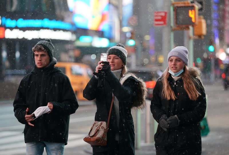 Snow begins to fall in Times Square during a Nor'easter, in New York City