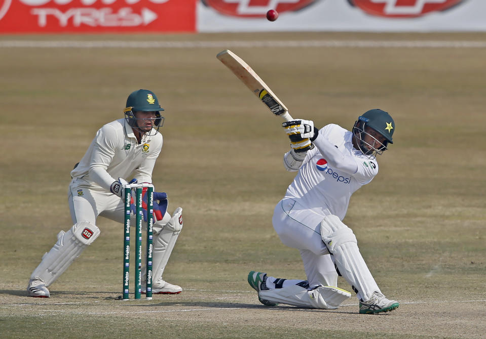 Pakistan's Nauman Ali, right, plays a shot for six while South Africa's Quinton de Kock watches during the fourth day of the second cricket test match between Pakistan and South Africa at the Pindi Stadium in Rawalpindi, Pakistan, Sunday, Feb. 7, 2021. (AP Photo/Anjum Naveed)