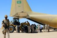 A picture taken on February 8, 2018 shows Saudi soldiers standing guard as workers unload aid from a Saudi air force cargo plane at an airfield in Yemen's central province of Marib (AFP/ABDULLAH AL-QADRY)