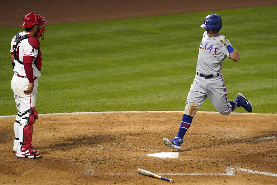 Texas Rangers' Nick Solak, right, scores on a sacrifice fly hit by Jose Trevino as Los Angeles Angels catcher Kurt Suzuki stands at the plate during the sixth inning of a baseball game Monday, April 19, 2021, in Anaheim, Calif. (AP Photo/Mark J. Terrill)