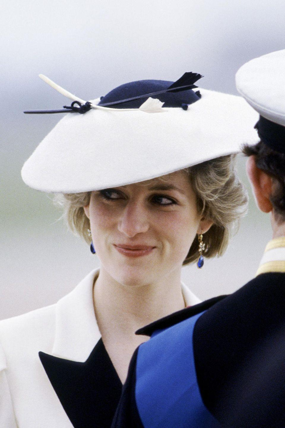 <p>At Heathrow Airport in an intricate navy-and-white saucer hat.</p>
