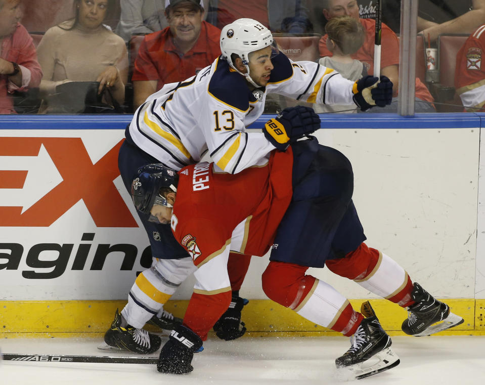 Florida Panthers defenseman Alexander Petrovic, bottom, slams Buffalo Sabres right wing Nicholas Baptiste (13) into the boards during the third period of an NHL hockey game, Friday, March 2, 2018, in Sunrise, Fla. (AP Photo/Wilfredo Lee)