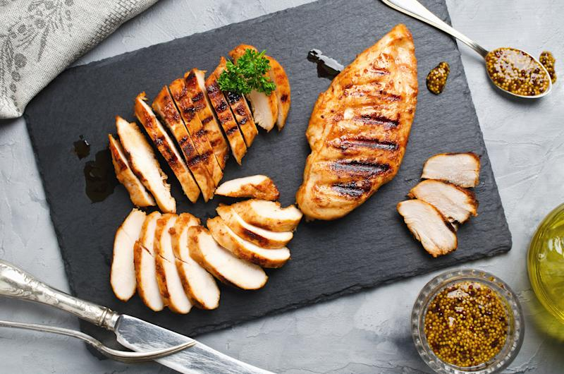 A photo of cooked and sliced chicken breast on a slate platter.