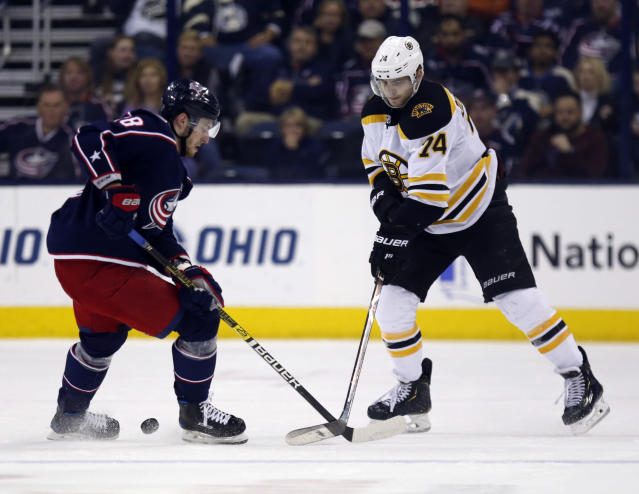 Boston Bruins forward Jake DeBrusk, right, passes against Columbus Blue Jackets forward Pierre-Luc Dubois, left, during the second period of an NHL hockey game in Columbus, Ohio, Tuesday, April 2, 2019. (AP Photo/Paul Vernon)