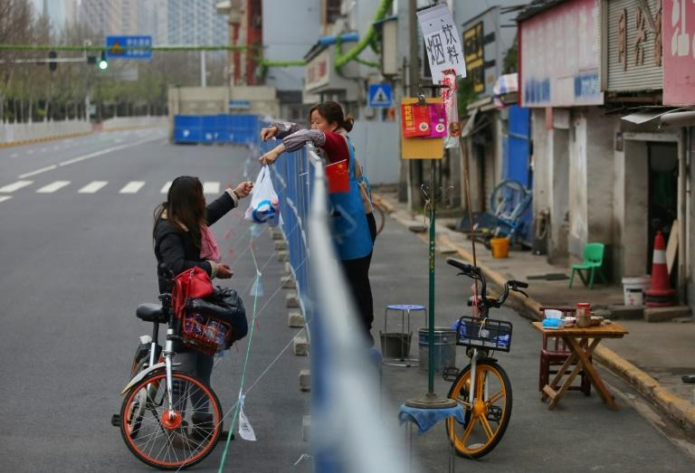 Barriers to stop the spread of the coronavirus in Wuhan have divided communities
