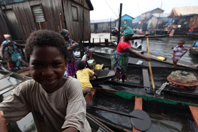 A child smiles as canoes float past in the floating slum of Makoko in Lagos, Nigeria, on Thursday, Sept. 27, 2012. A group is planning to build a floating school in the slum, which state authorities have targeted for demolition in the past. (AP Photo/Jon Gambrell)
