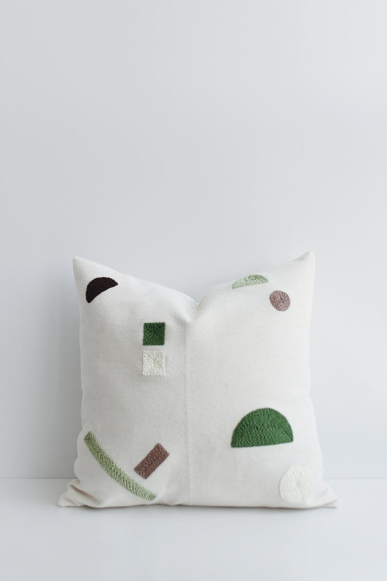 """For those who are tentative to commit to bold color, this embroidered geometric pillow from Etsy adds just a dash. <br><br><strong>ArceLiving</strong> Abstract Geometric Punch Needle Embroidery Pillow, $, available at <a href=""""https://go.skimresources.com/?id=30283X879131&url=https%3A%2F%2Fwww.etsy.com%2Flisting%2F703529381%2Fabstract-geometric-punch-needle"""" rel=""""nofollow noopener"""" target=""""_blank"""" data-ylk=""""slk:Etsy"""" class=""""link rapid-noclick-resp"""">Etsy</a>"""