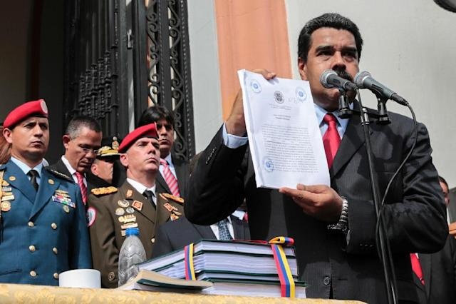 Venezuelan President Nicolas Maduro shows the books with the national budget for 2017 at the National Pantheon in Caracas, on October 14, 2016 (AFP Photo/Yoset Montes)