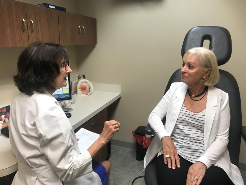 FILE - In this July 17, 2019, file photo, Laurie Barber, a Little Rock, Ark., ophthalmologist, talks with patient Carolyn Lay at the Little Rock Eye Clinic. Barber chairs a group that wants to hold a referendum on a new Arkansas law that expands the procedures that optometrists can perform. Arkansas election officials on Friday, Aug. 2, 2019, rejected the attempt to hold a referendum next year on a new state law expanding what procedures optometrists can perform that has sparked an unusually expensive and public lobbying fight. (AP Photo/Andrew DeMillo, File)