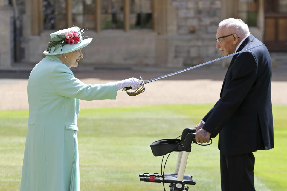 Captain Sir Thomas Moore receives his knighthood from Britain's Queen Elizabeth, during a ceremony at Windsor Castle in Windsor, England, Friday, July 17, 2020. Captain Sir Tom raised almost £33 million for health service charities by walking laps of his Bedfordshire garden. (Chris Jackson/Pool Photo via AP)