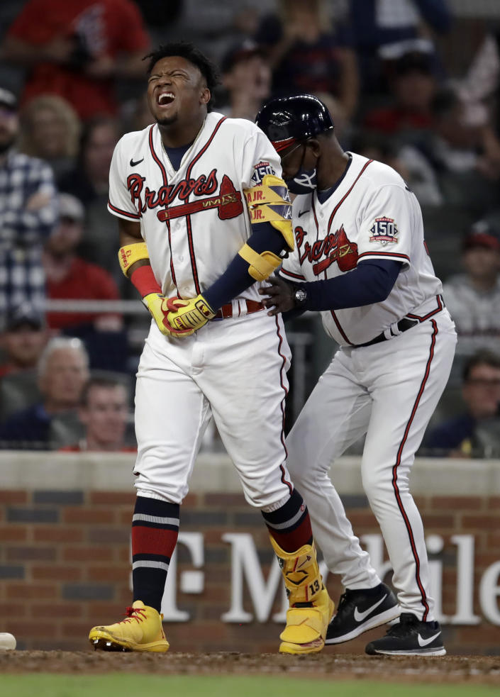 Atlanta Braves' Ronald Acuna Jr., left, is assisted by third base coach Ron Washington after being hit by a pitch thrown by Philadelphia Phillies' Sam Coonrod in the seventh inning of a baseball game Saturday, May 8, 2021, in Atlanta. (AP Photo/Ben Margot)