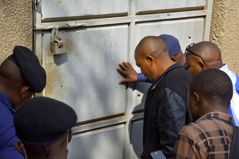 Congolese security officers look at a broken door at the Kangbayi central prison in Beni
