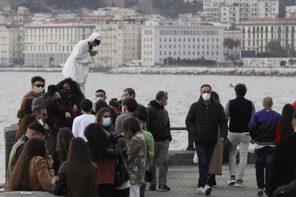 """People stroll along Viale Caracciolo overlooking the Gulf of iNaples, Italy, Saturday, Nov. 14, 2020. Along the Naples waterfront, Luigi Orefice perched his 4-year-old son, Giovanni, on the thick wall lining the promenade. With fog ringing the Vesuvius volcano in the background, the postcard-like panorama would be familiar to tourists. But his job delivering beverages to hospitals lets Orefice see the ugly realities beyond the """"O Sole Mio"""" image tourists might have of the south. (AP Photo/Gregorio Borgia)"""