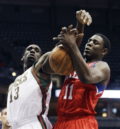 Philadelphia 76ers' Jrue Holiday and Milwaukee Bucks' Ekpe Udoh (13) compete for a rebound during the first half of an NBA basketball game, Wednesday, April 25, 2012, in Milwaukee. (AP Photo/Morry Gash)