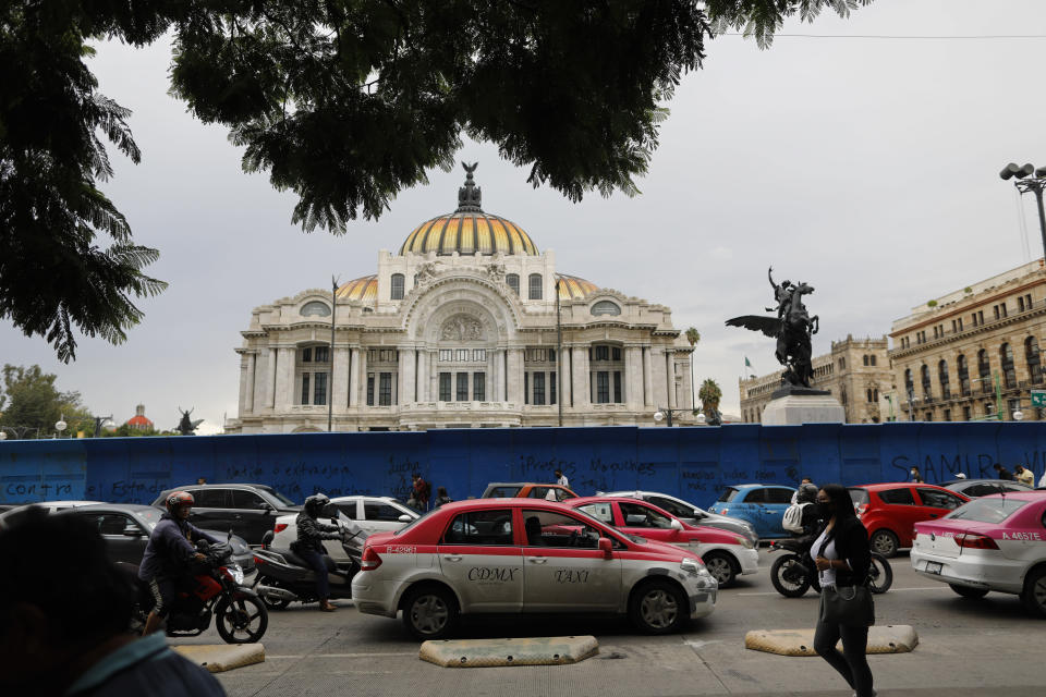 """Pedestrians and cars pass in front of the Palace of Fine Arts amidst the """"new normal"""" of the ongoing coronavirus pandemic, in central Mexico City, Monday, Aug. 10, 2020. (AP Photo/Rebecca Blackwell)"""