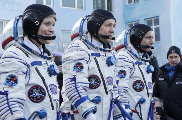 U.S. astronaut Anne McClain, left, Russian cosmonaut Оleg Kononenko, centre, and CSA astronaut David Saint Jacques, members of the main crew of the expedition to the International Space Station (ISS), report to members of the State Committee prior to the launch of Soyuz MS-11 space ship at the Russian leased Baikonur cosmodrome, Kazakhstan, Monday, Dec. 3, 2018. (AP Photo/Dmitri Lovetsky, Pool)