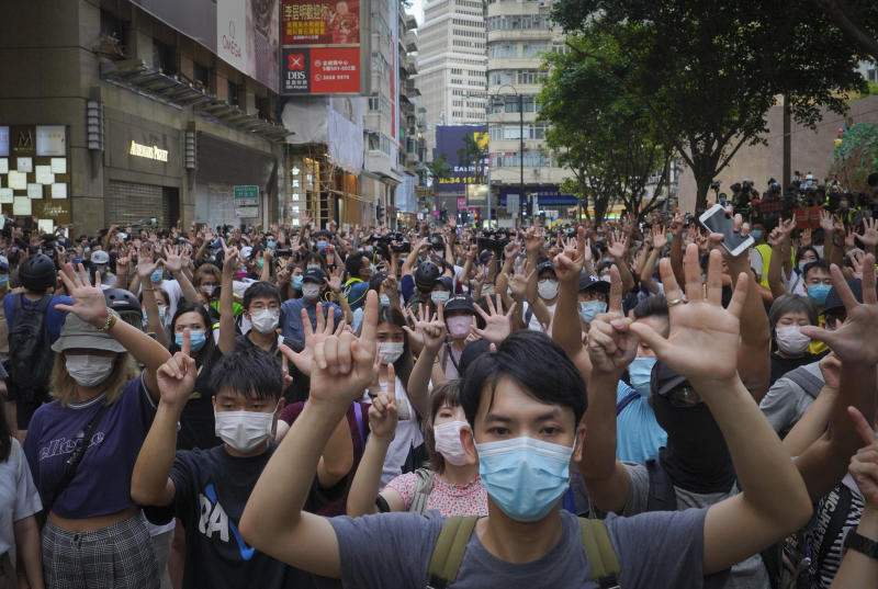 "Protesters against the new national security law gesture with five fingers, signifying the ""Five demands - not one less"" on the anniversary of Hong Kong's handover to China from Britain in Hong Kong, Wednesday, July. 1, 2020. Hong Kong marked the 23rd anniversary of its handover to China in 1997, and just one day after China enacted a national security law that cracks down on protests in the territory. (AP Photo/Vincent Yu)"