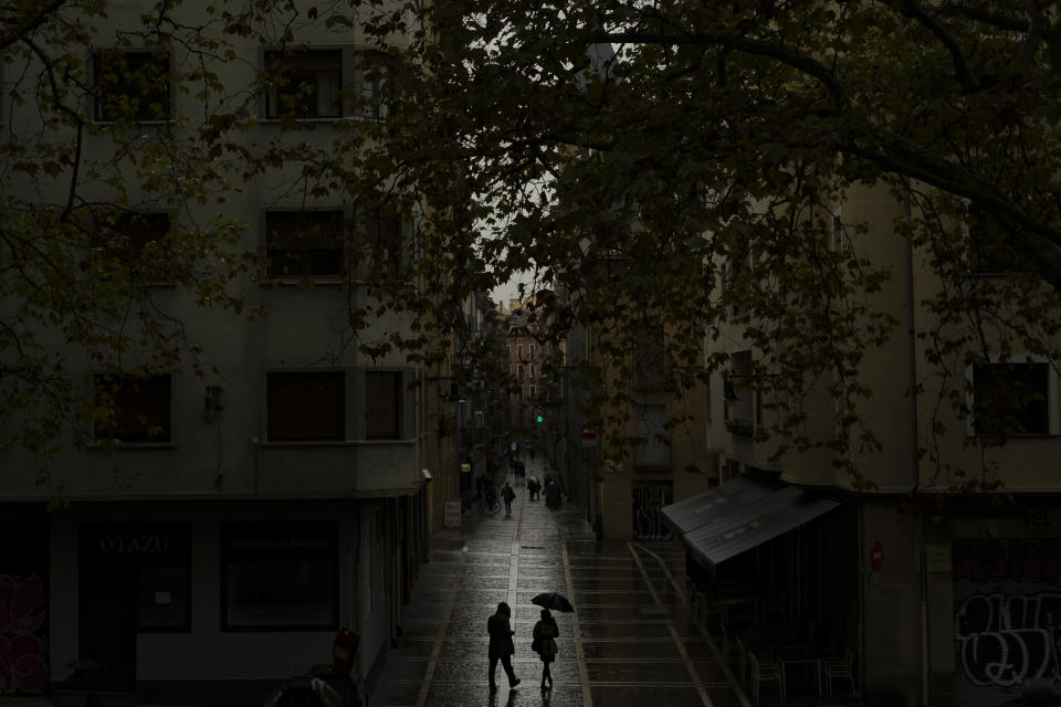 Pedestrian shelters from the rain under an umbrella while walking along the old city during a raining autumn day, in Pamplona, northern Spain, Saturday, Oct. 3, 2020. (AP Photo/Alvaro Barrientos)