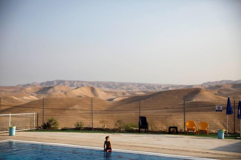 FILE PHOTO: A boy sits by the swimming pool at the Israeli settlement of Vered Yericho in the occupied West Bank