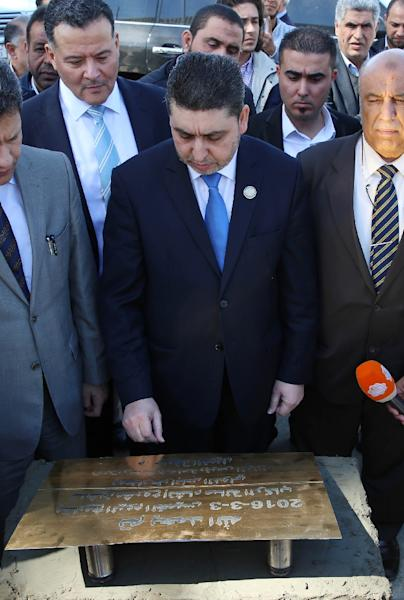 The leader of the Tripoli-based unrecognised Libyan government, Khalifa al-Ghweil (C), stands next to a foundation stone for the reconstruction of Tripoli International Airport (AFP Photo/)