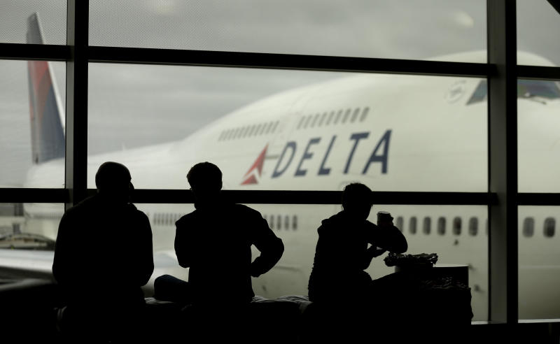 FILE - In this Monday, Oct. 29, 2012, file photo, travelers on Delta Airlines waits for flights, in Detroit. Delta said Superstorm Sandy hurt fourth-quarter profits by $100 million in 2012. That, plus special charges, left Delta Air Lines Inc. with a profit of just $7 million.  (AP Photo/Charlie Riedel, file)