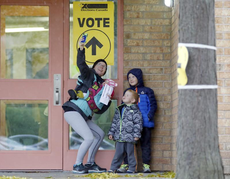 Alexandra Pettit takes a selfie with her kids at the Gloucester Presbyterian Church polling station, in Ottawa, after casting her vote in the Canadian federal election on Monday, Oct. 19, 2015. THE CANADIAN PRESS/ Patrick Doyle