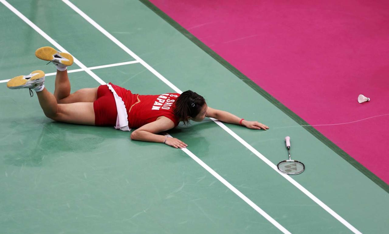 Japan's Sayaka Sato falls during play against Britain's Susan Egelstaff during their women's singles group play stage Group H badminton match during the London 2012 Olympic Games at the Wembley Arena July 31, 2012.    REUTERS/Bazuki Muhammad (BRITAIN  - Tags: SPORT BADMINTON SPORT OLYMPICS)