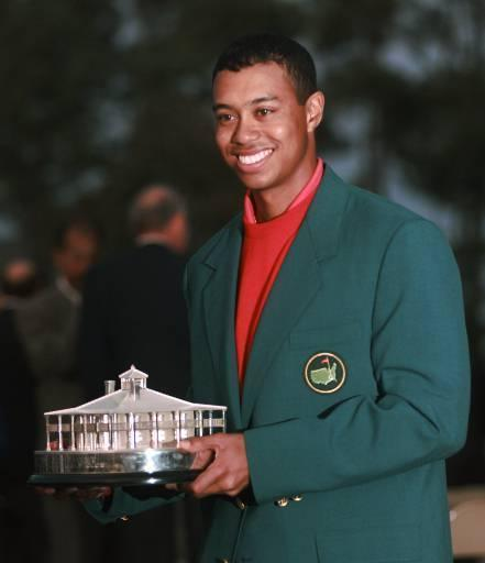 FILE - In this April 13, 1997 file photo, Masters champion Tiger Woods holding a replica of the Masters Trophy after winning the golf tournament at the Augusta National Golf Club in Augusta, Ga. It has been 20 years since Woods won the Masters for the first time by a record 12 shots. (AP Photo/Bill Waugh, File)