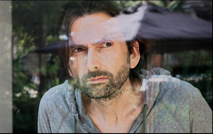 """David Tennant looks out a window in """"Staged."""""""