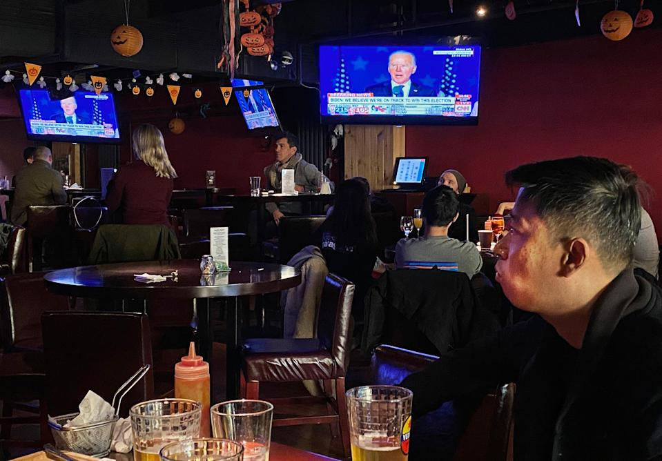 Customers watch television during an election watching event at a local bar on Nov. 4 in Beijing