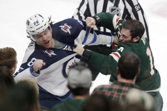 Winnipeg Jets defenseman Nathan Beaulieu (88) and Minnesota Wild center Luke Kunin (19) fight in the third period of an NHL hockey game Saturday, Dec. 21, 2019, in St. Paul, Minn. The Jets defeated the Wild 6-0. (AP Photo/Andy Clayton-King)